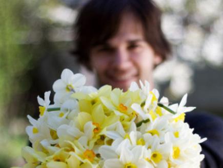 גבר מחזיק פרחים- קלישאות בערב החג (צילום: pierredesvarre, Istock)