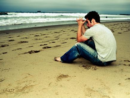 גבר יושב על שפת הים (צילום: Kris Hanke, Istock)