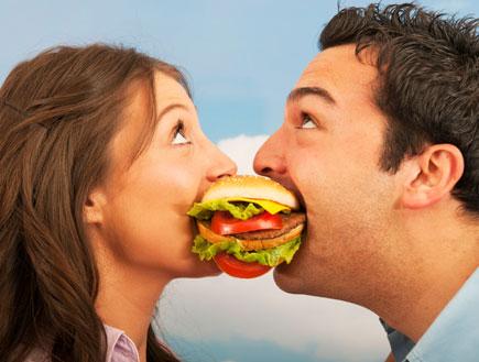 אישה וגבר נוגסים בהמבורגר (צילום: 101cats, Istock)