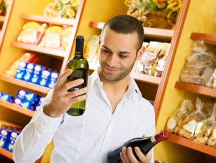 גבר מחזיק בקבוק יין