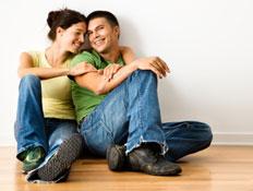 זוג מחויך יושב על פרקט