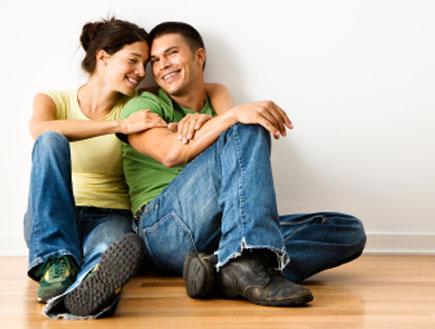 זוג מחויך יושב על פרקט (צילום: iofoto, Istock)