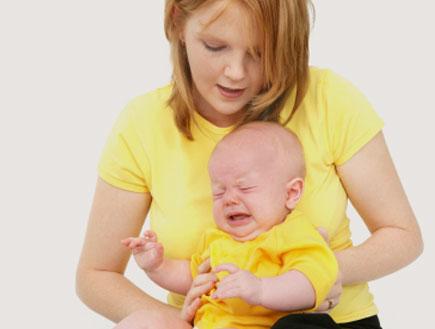 אישה בצהוב מחזיקה תינוק צורח בצהוב (צילום: hidesy, Istock)
