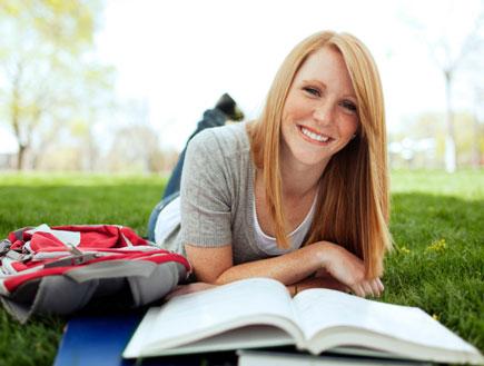 סטודנטית על הדשא (צילום: Andrew Rich, Istock)