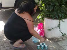 אישה מניחה נרות זיכרון ליד ביתם של משפחת אושרנקו
