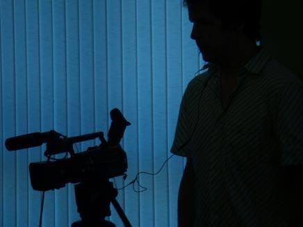 עומד בחושך עם מצלמת וידאו (עמית ולדמן) (צילום: עמית ולדמן)