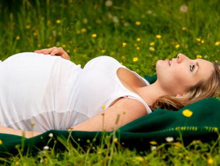 אישה בהריון על הדשא (צילום: istockphoto)