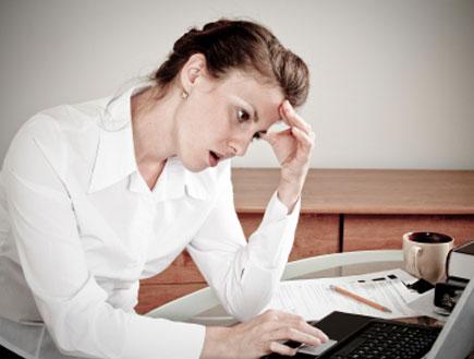 אישה מול מחשב מחזיקה את הראש (צילום: Pawel Gaul, Istock)