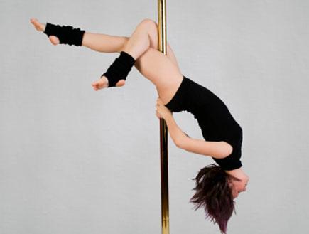 סטריפדאנס- בחורה בבגד שחור מתנדנדת על עמוד (צילום: istockphoto)