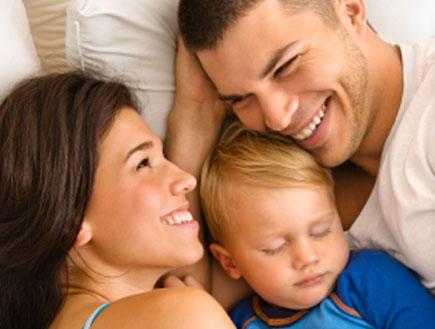 זוג ותינוק במיטה (צילום: Fotosearch, Istock)