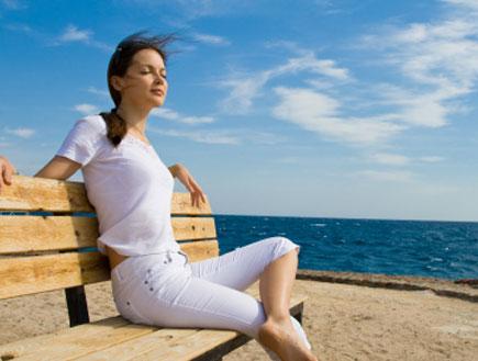 אישה בים מביטה בגלים (צילום: istockphoto)