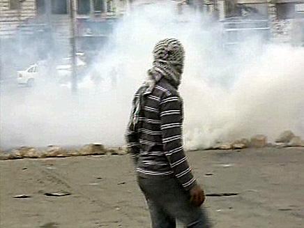 """פלסטיני מיידה אבנים לעבר חיילי צה""""ל בחברון (צילום: חדשות 2)"""