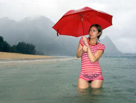 אישה עם מטריה בים - חופשה מבאסת (צילום: Trevor Hunt, Istock)