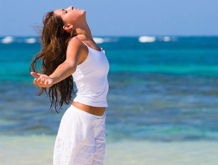 אשה נושמת על החוף (צילום: apomares, Istock)