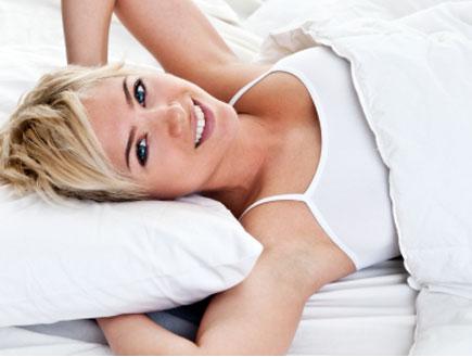 אישה מחייכת במיטה (צילום: John Sommer, Istock)