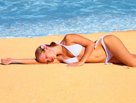 אישה שוכבת על החוף