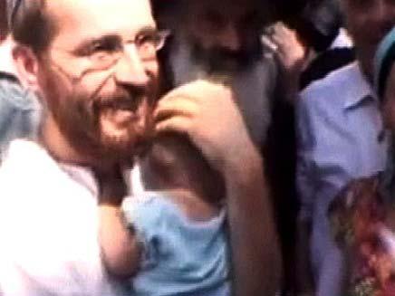 חיים פרלמן מחזיק את הבן שלו (צילום: חדשות 2)