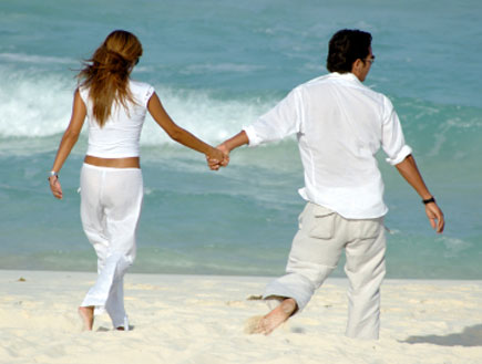 בחור ובחורה צועדים יד ביד בחוף הים (צילום: rarpia, Istock)
