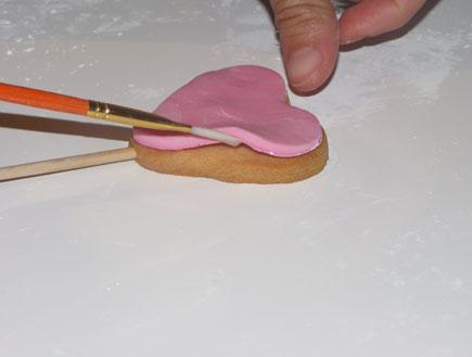 עוגיות על מקל - מדביקים את בצק הסוכר לעוגייה (צילום: ג'יג'י בייקרי)