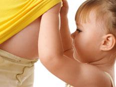 ילדה מסתכלת על הבטן של אמא בהריון (צילום: Kobyakov, Istock)