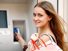 בחורה מושכת כסף מהכספומט (צילום: Damir Cudic, Istock)