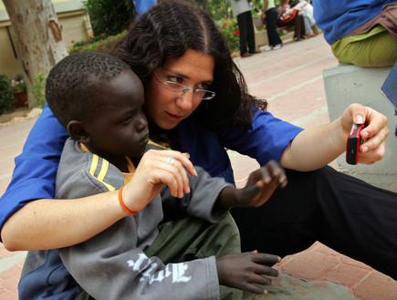 חניכת תנועת הנוער העובד משחקת עם פליט סודני בבאר שבע (צילום: David Silverman, GettyImages IL)