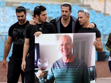 """משפחת כהן עם התמונה של אבי ז""""ל (יניב גונן) (צילום: מערכת ONE)"""
