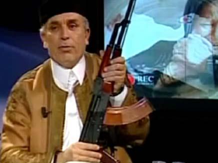 מגיש מהדורת חדשות עם מיקרופון וקלצ'ניקוב, לוב (צילום: חדשות 2)