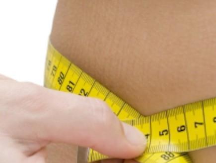 בחורה מודדת את היקף הבטן (צילום: winterling, Istock)
