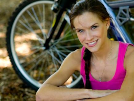 אשה עם אופניים (צילום: ChrisBoswell, Istock)
