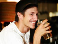 גבר שותה בירה ומחייך (צילום: istockphoto)