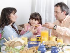 הורים וילדה יושבים בשולחן ואוכלים (צילום: Grafissimo, Istock)