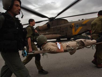 צוות חיילים מחלצים עם אלונקה ברקע מסוק