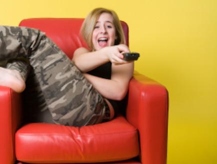 נערה צופה בטלוויזיה (צילום: Claude Dagenais, Istock)