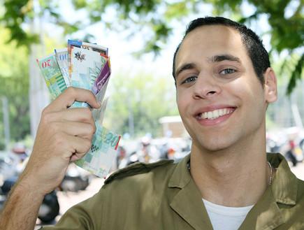 """חייל צנחנים מחזיק שטרות ביד מחייך (צילום: עודד קרני, פז""""ם)"""