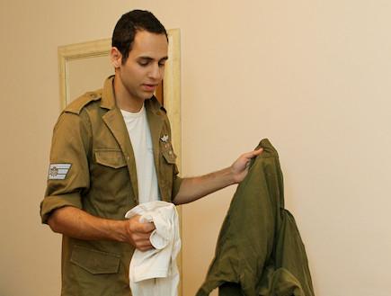 חייל מכניס בגדים לתיק