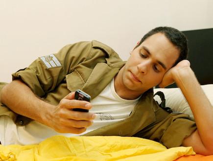 """חייל על מיטה מסתכל על הטלפון  (צילום: עודד קרני, פז""""ם)"""