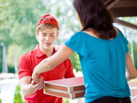 שליח פיצה מקבל טיפ (צילום: Izabela Habur, Istock)