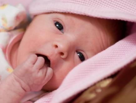 תינוקת מסתכלת דרך שמיכה (צילום: Daniel Brunner, Istock)
