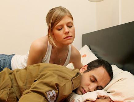 """בחורה עצובה שוכבת במיטה חבר שלה חייל ישן ברקע (צילום: עודד קרני, פז""""ם)"""