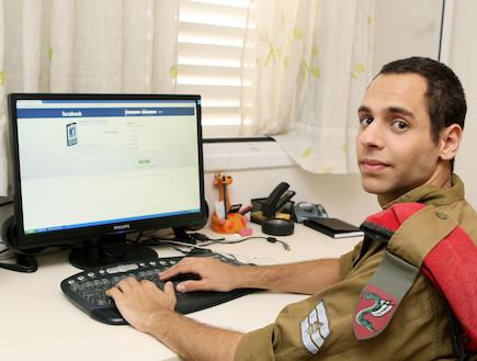"""חייל מול מחשב בפייסבוק מסתכל למצלמה  (צילום: עודד קרני, פז""""ם)"""