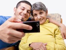 אישה מבוגרת וגבר צעיר יושבים ומסתכלים בטלפון הנייד