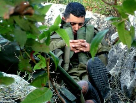 פזם חייל עם אפוד ישן בין שיחים