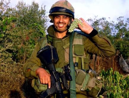 פזם חייל בכוננות מחזיק אשכול ענבים