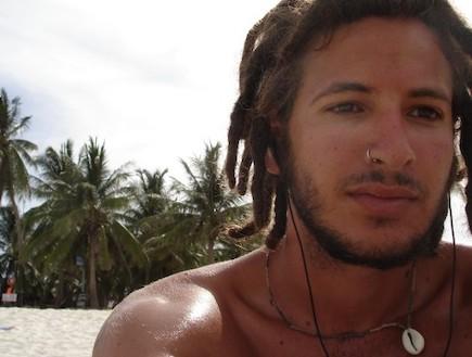 פזם צעיר עם נזם בחוף ים רקע דקלים