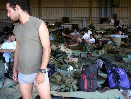 פזם חיילי מילואים בלבוש אזרחי בהאנגר מלא תיקים