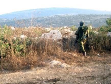 פזם חייל עומד ברקע שיחים והרים