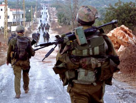 פזם חיילים עם אפודים הולכים בשטח בנוי