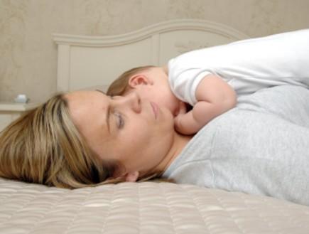 אישה עם תינוק בן יומו שוכבת במיטה (צילום: Lisa Valder, Istock)