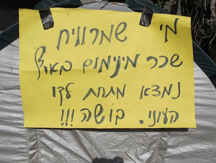 שלטי המחאה - מי שמרוויח שכר מינימום מתחת קו העוני (צילום: mako)